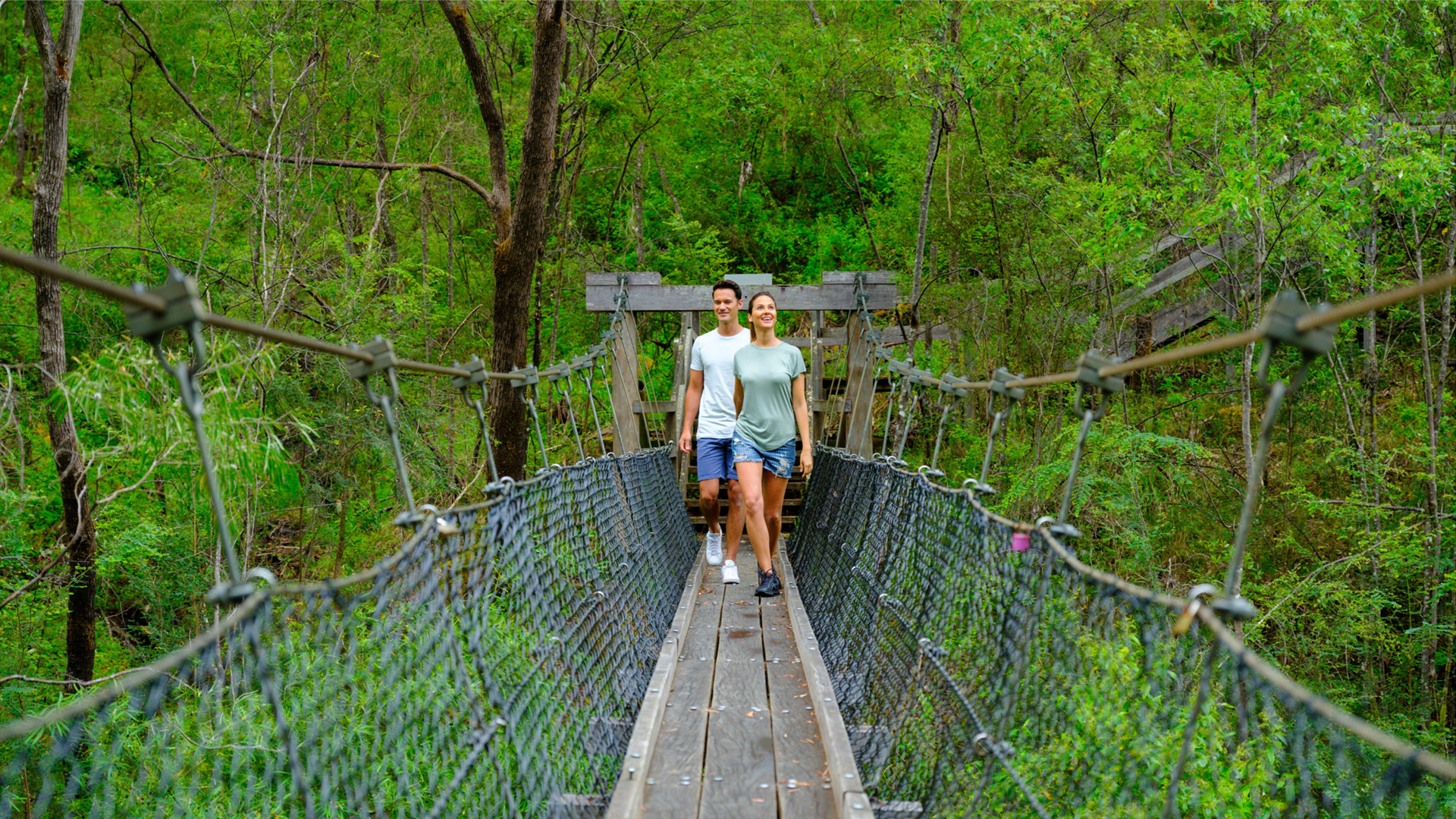 Couple crossing bridge in south west forrest